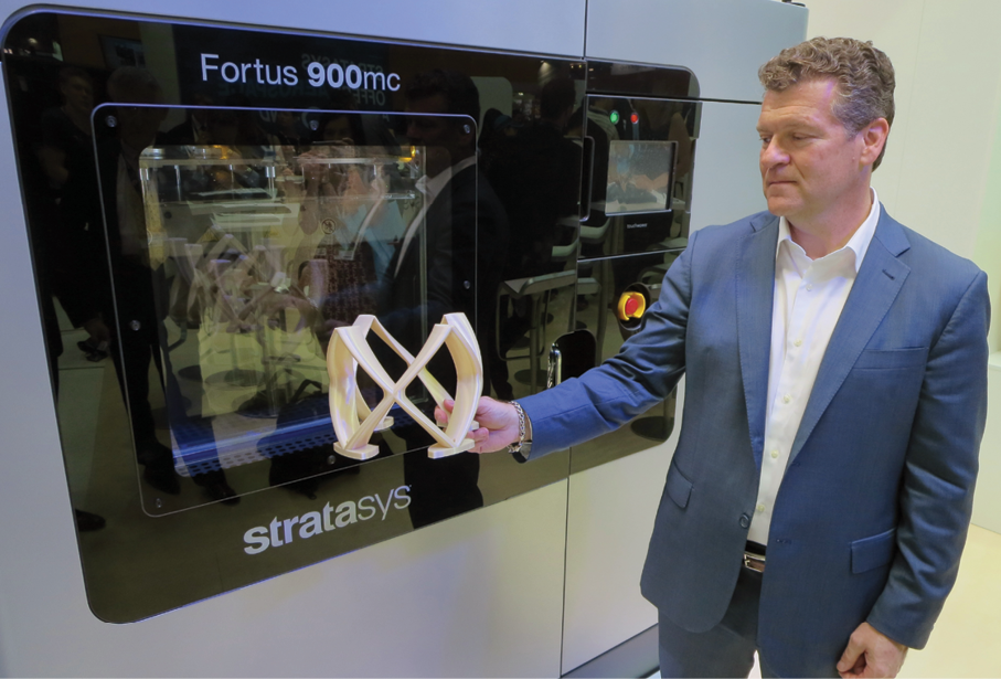 Jim Vurpillat of Stratasys shows the Fortus 900mc system with a camera mounting bracket produced from ULTEM 9085.
